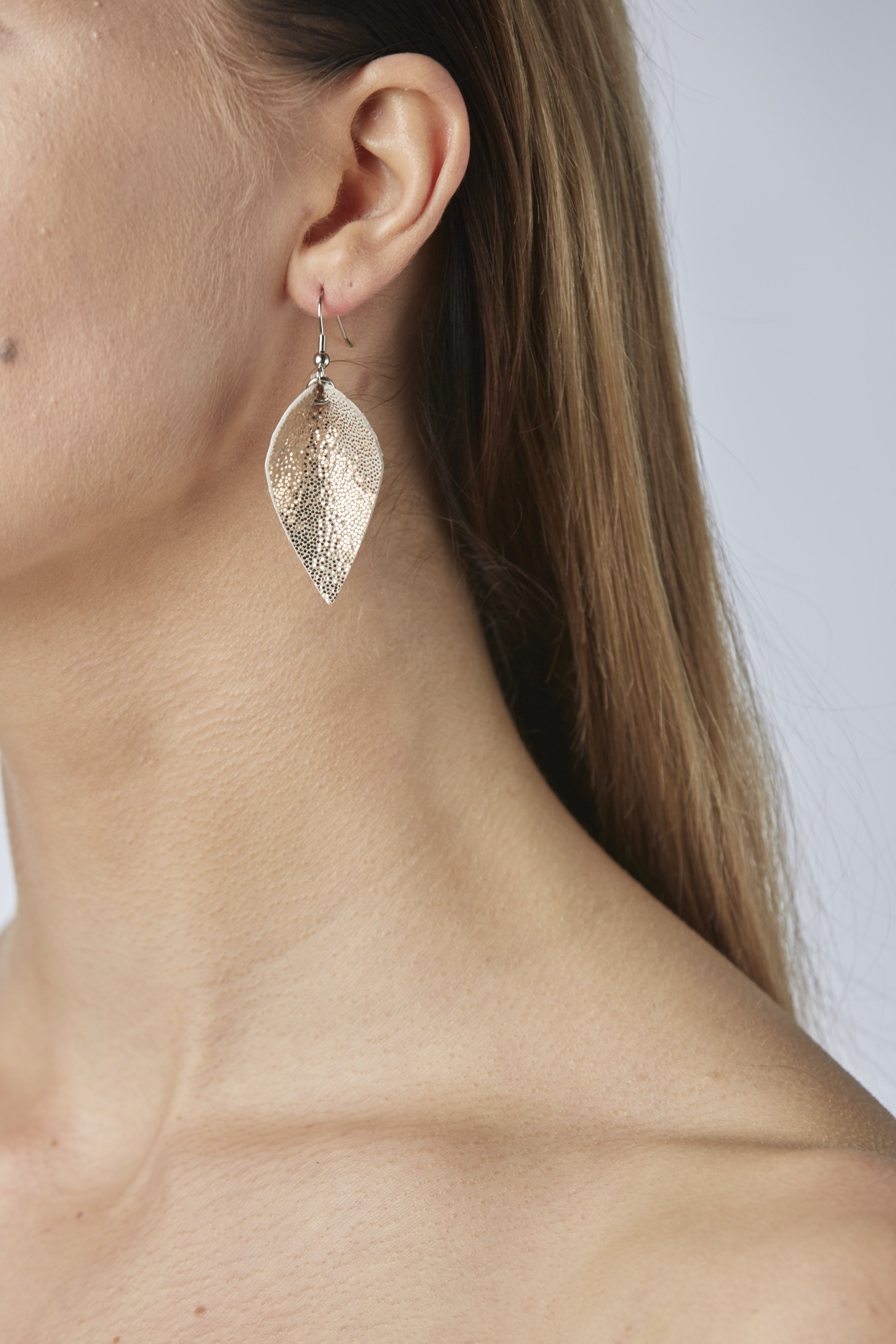 Lumme Petite earrings in glitter gold are inspired by the most beautiful decoration of Finland´s lakes, the water lily – Lumme.These lightweight exclusive Italian goat leather made elegant earrings size is ideal for everyone to wear.